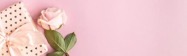 ピンクの背景に1つのバラとお祝いのバナー。上面図、フラットレイ。スペースをコピーします。誕生日、母親、バレンタイン、女性、結婚式の日のコンセプト。