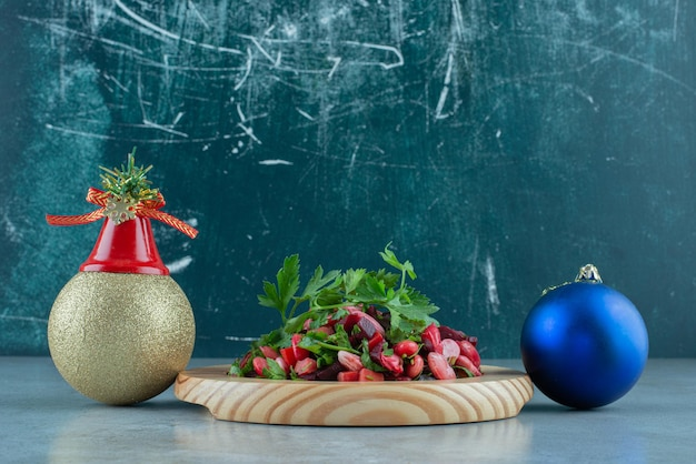 Palline festive accanto a un piatto di insalata di vinegret ricoperta di prezzemolo su marmo.