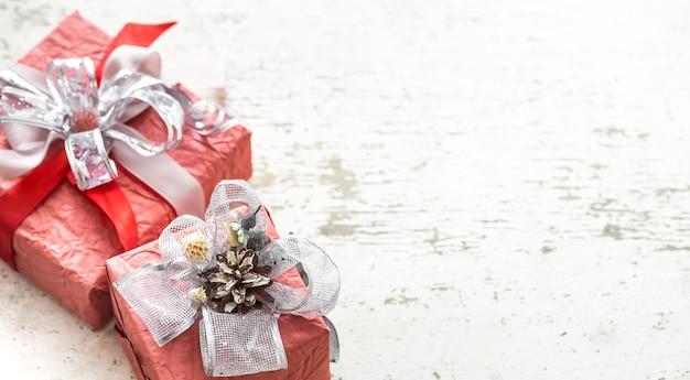 Belle scatole regalo festive con un fiocco su uno sfondo di legno chiaro.