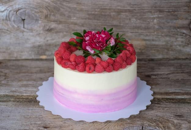 흰색과 보라색 크림이있는 축제 아름다운 수제 케이크, 나무 딸기 열매와 라이브 붉은 장미로 장식