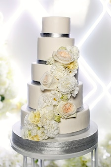 Festive beautiful  wedding cake decorated with flowers isolated close up. white tiered wedding cake isolated .candy bar on the wedding party. wedding day.
