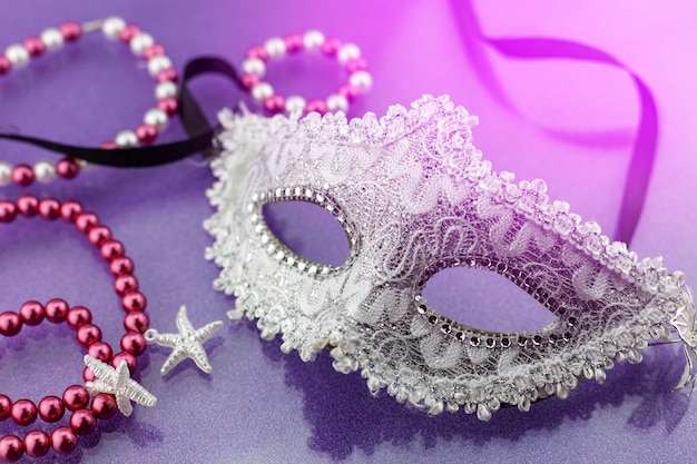 A festive, beautiful white mardi gras or carnival mask on beautiful colorful paper
