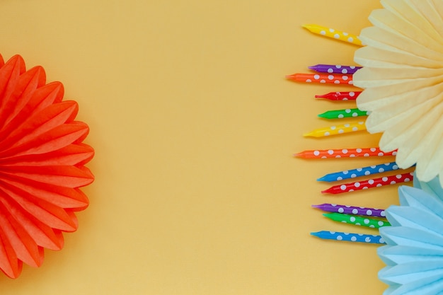パステルイエローの誕生日やパーティーでお祝いの誕生日カラフルなキャンドルと紙のファン