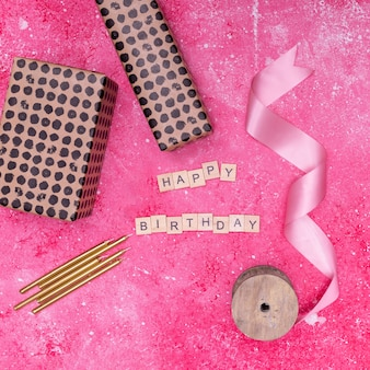 Festive birthday supplies on pink marble background
