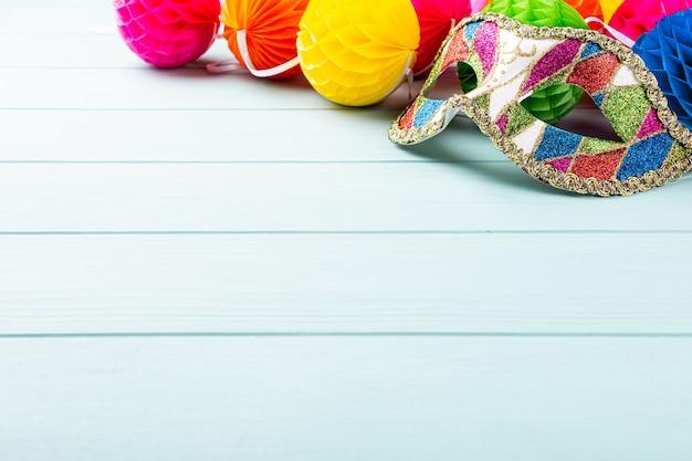 Праздничная синяя поверхность с красочной карнавальной маской и шариками из перца. концепция поздравительной открытки для дня рождения, карнавала, вечеринки, приглашения