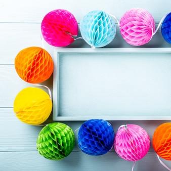 Праздничная синяя поверхность с красочными бумажными шарами. концепция поздравительной открытки для дня рождения, вечеринки, приглашения, карнавала. копирование пространства, вид сверху, плоская планировка
