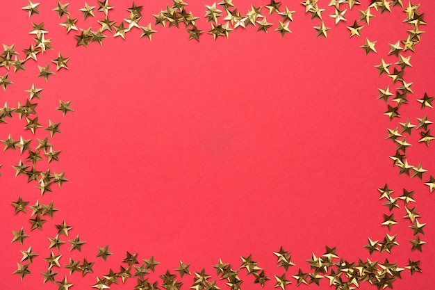 Festive border of golden stars glitter confetti on red background. xmas holiday .