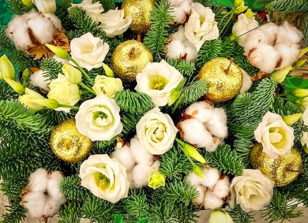 황금 사과와 녹색 가문비나무 전나무가 있는 크리스마스 휴일 흰 장미를 위한 축제 꽃다발