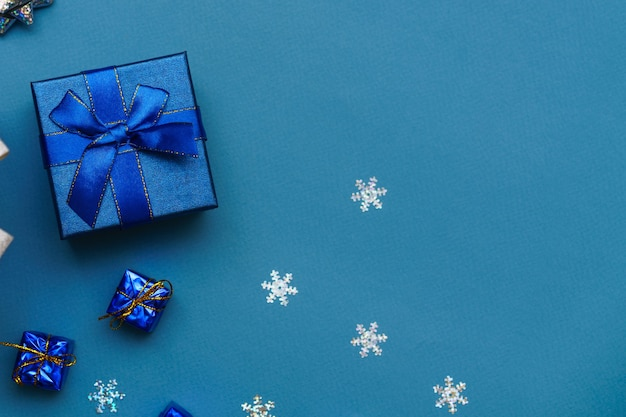 Festive box close up blue bow on blue background with christmas balls and snowflakes new year christ...