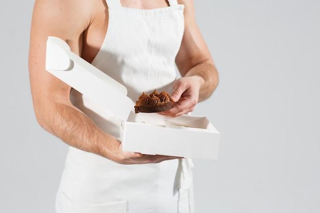 エプロンの男の手にタルトが付いたお祝いボックス。男性がタルトを1つ取り出します。ホームベーキングの快適さ。閉じる。デザートとお菓子の手。パティシエの手、デザートのパッキング。