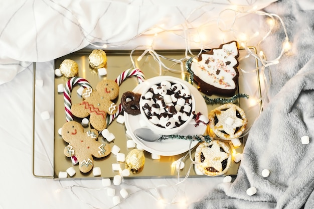 Festive breakfast in bed with hot chocolate, marshmallow, mince pie, gingerbread man and sweets