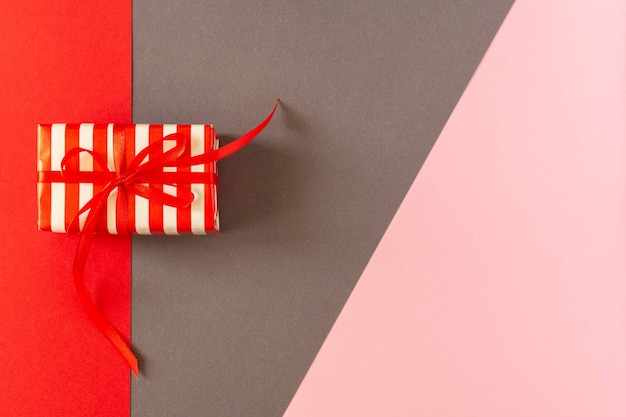 Festive bright colorful background, gift with ribbon and bow on colored papers