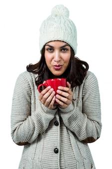 Festive brunette holding hot drink