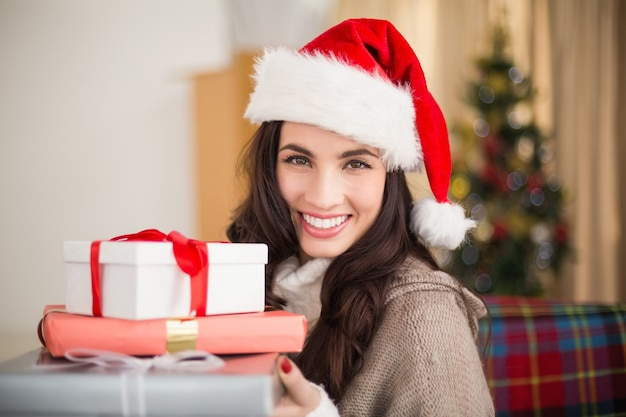 Festive brunette holding pile of gifts at christmas