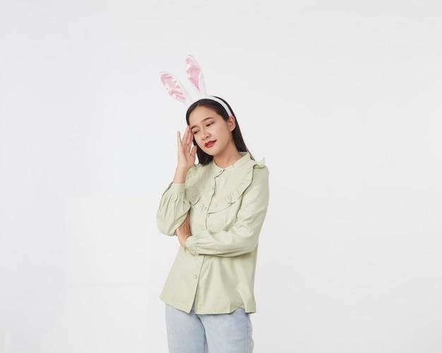 축제 토끼와 계란 시즌. 흰색 표면에 부활절과 부활절 토끼 귀에 세로 아름 다운 젊은 아시아 여자