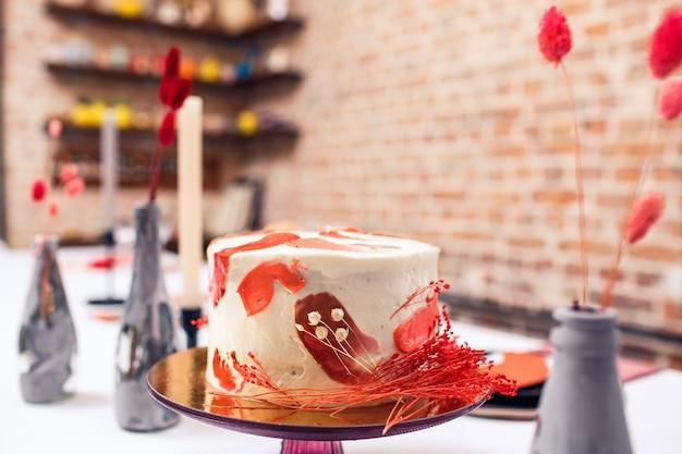 Праздничный торт красного цвета на банкетном столе. интерьер ресторана.