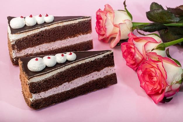 초콜릿과 코티지 치즈 층이있는 축제 케이크. 두 부분. 분홍색 배경에. 생일, 공휴일, 과자. 공간을 복사하십시오.