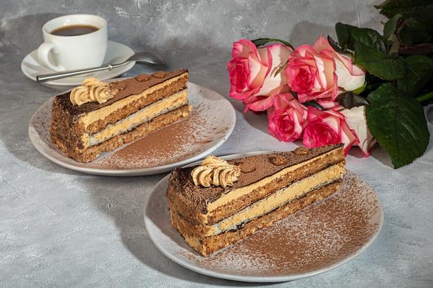 초콜렛과 바삭한 중간층이있는 축제 케이크. 두 부분. 회색 배경. 생일, 공휴일, 과자. 공간을 복사하십시오.