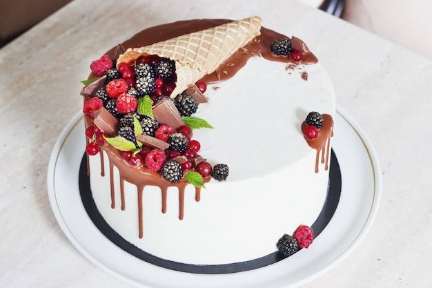 Festive cake with chocolate and berries in a waffle horn