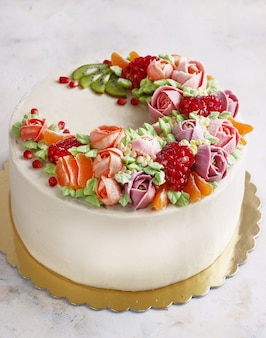 Festive cake with cream flowers and fruits on a light