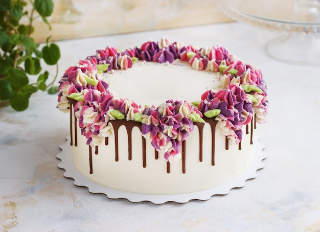 Festive cake with cream flowers hydrangea on light
