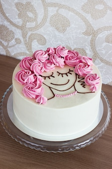 Festive cake with flowers from meringue and a girl face on light