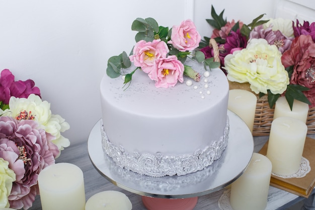 Festive cake with  mastic is decorated with pink flowers close up.  beautiful delicious cake decoratrd with roses on birhtday or wedding party. candy bar on the festive table.