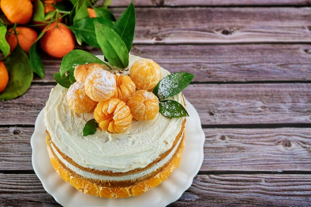 Festive cake with whole tangerines on wooden table