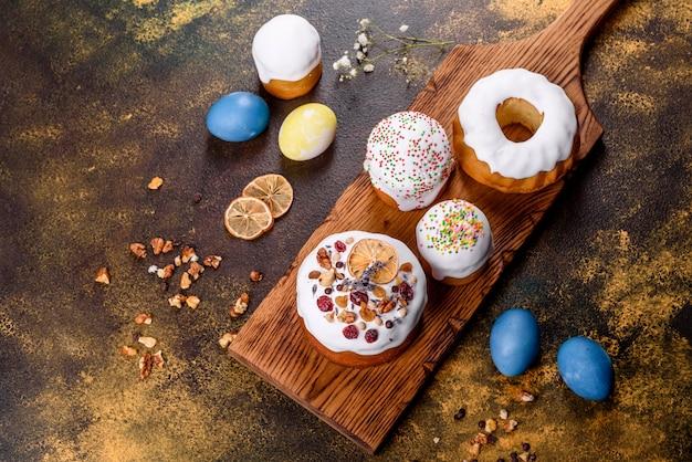 Праздничные торты с белой глазурью, орехами и изюмом с пасхальными яйцами на праздничном столе. подготовка к пасхе