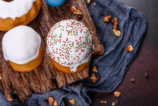 Праздничные торты с белой глазурью, орехами и изюмом с пасхальными яйцами на праздничном столе. приготовления к пасхе