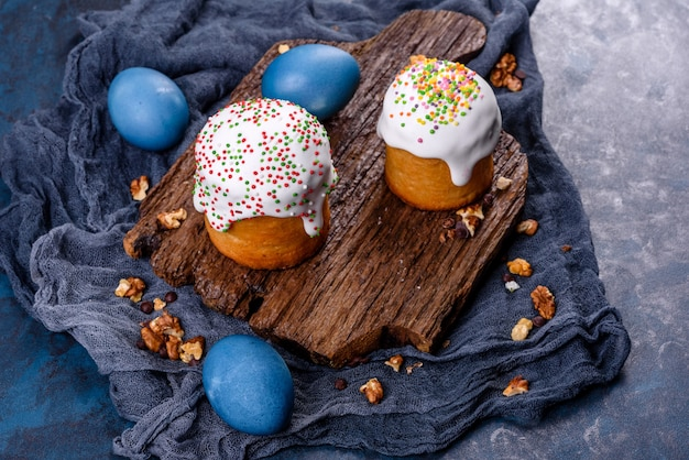 Праздничные торты с белой глазурью, орехами и изюмом с пасхальными яйцами на праздничном столе