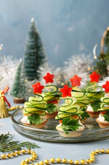 Festive canapes in the shape of christmas trees made of cucumbers and stars of bell pepper on a light blue background with two glasses of wine, closeup