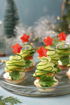 Festive canapes in the shape of christmas trees made of cucumbers and stars bell pepper on light blue table, closeup. vertical format