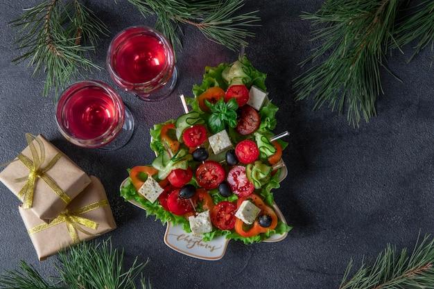 오이, 토마토, 치즈를 곁들인 축제 카나페는 짙은 회색 배경에 와인 두 잔과 함께 크리스마스 트리로 접시에 제공됩니다.
