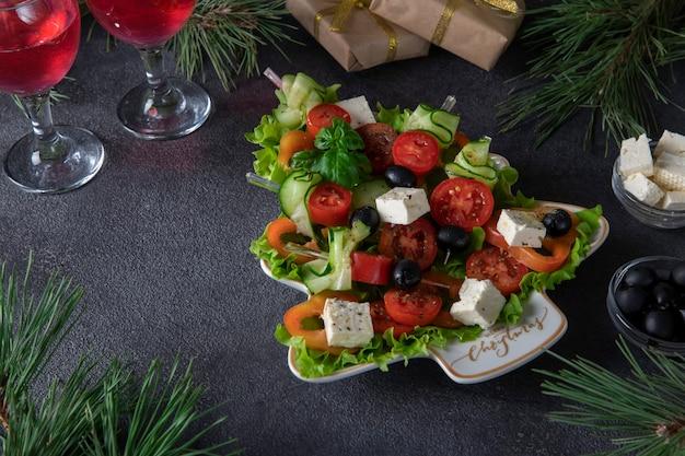 오이, 토마토, 치즈를 곁들인 축제 카나페는 두 잔의 와인과 함께 어두운 회색 배경에 크리스마스 트리로 접시에 제공됩니다.