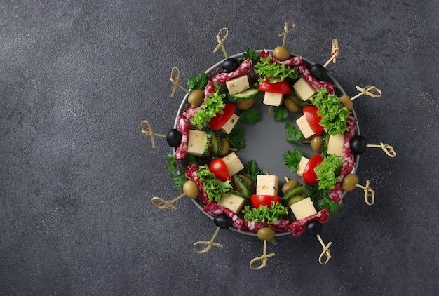 소시지, 오이, 토마토, 올리브, 치즈를 곁들인 축제 카나페는 어두운 배경에서 크리스마스 화환으로 접시에 제공됩니다. 평면도