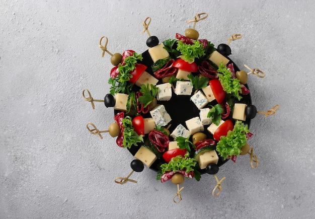 소시지, 오이, 토마토, 올리브, 치즈를 곁들인 축제 카나페는 밝은 회색 배경에 크리스마스 화환으로 접시에 제공됩니다. 평면도