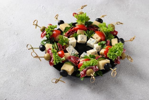소시지, 오이, 토마토, 올리브, 치즈를 곁들인 축제 카나페는 밝은 회색 배경에 크리스마스 화환으로 접시에 제공됩니다.
