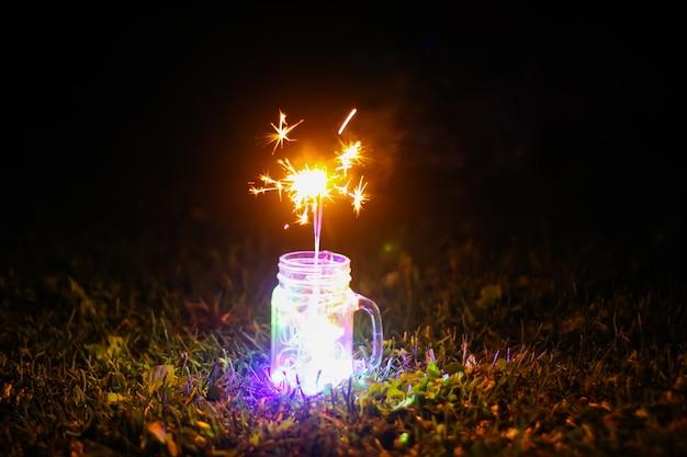 밤 자연 배경의 유리 항아리에 밝은 다채로운 화환 조명과 벵골어 불이 있는 축제 카드.
