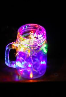 밤 자연 배경에 유리 항아리에 밝은 다채로운 화환 조명 축제 카드.