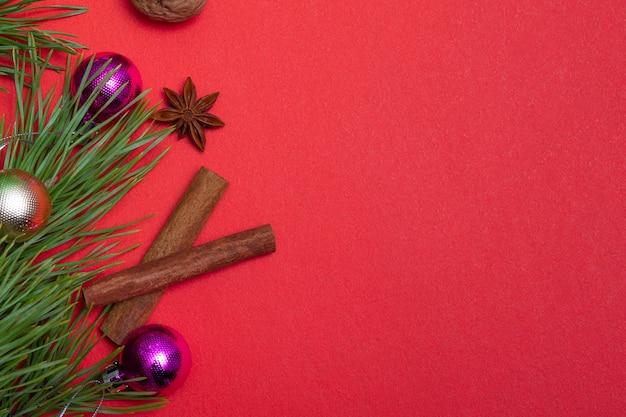色付きの背景にクリスマスの要素とコピースペースを持つお祭りカード。クリスマスラッピング、背景。クルミ、ドライオレンジ、シナモン、スターアニス。