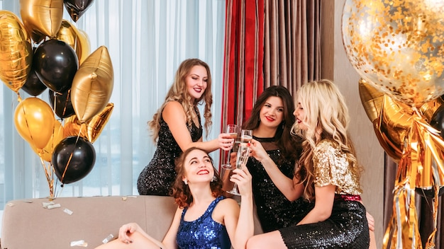 お祝いのお祝い。婚約者の周りに座って、彼女の幸せにスパークリングワインを飲む女性。