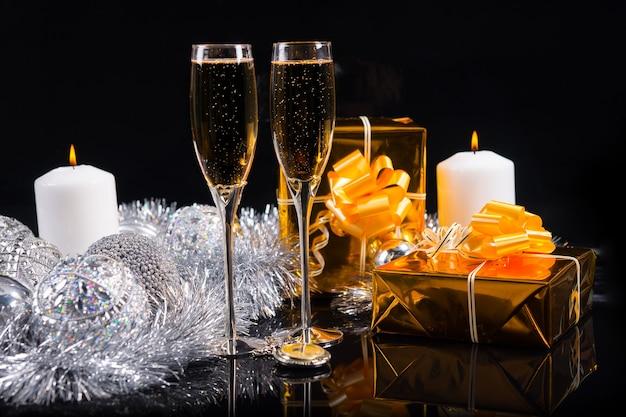 暗い反射背景に白いろうそくと銀の装飾を燃やす静物画のシャンパンの2つのフルートとクリスマスのお祝いのシャンパンの背景