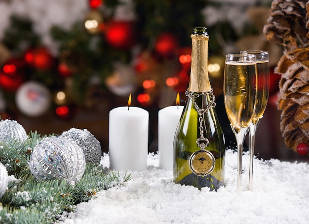 Festive champagne and candles on snowy surface