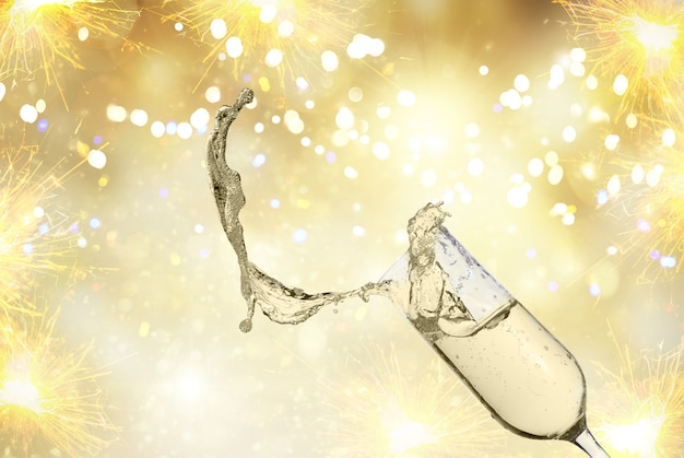 Festive champagne glas with splash on golden bokeh background with lights