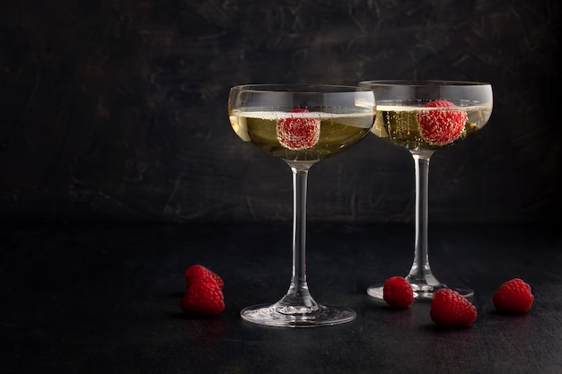 Festive champagne glasses with raspberries