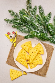 Festive cheese crackers, new year snack concept. cookies, mouse figure, fir tree branch, artificial snow, sackcloth napkin.