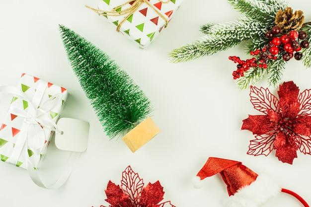 축제 크리스마스와 새해 배경, 미니 전나무의 꼭대기, 포장된 기트, 산타 모자, 흰색 바탕에 붉은 꽃