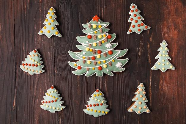Праздничные рождественские и новогодние пряники в форме ели, плоской планировки, на деревянном коричневом фоне.