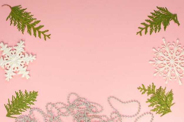 축제 크리스마스 배경, 전나무 가지, 하얀 눈송이, 분홍색 배경에 은색 장식 구슬, 평평한 평지, 위쪽 전망